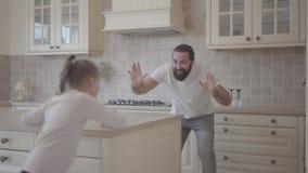 愉快的逗人喜爱的有女儿和她滑稽的父亲跑,笑和在美丽的现代厨房的乐趣torether 股票录像