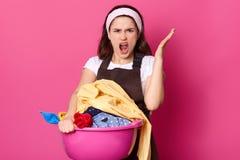 懊恼美女在不满情绪举充满愤怒的手,感觉哺养洗涤的衣裳,劳累过度,惊叹, 库存照片