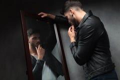 敬佩的自我陶醉者性感的年轻人在镜子 图库摄影