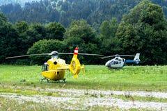 救护车和在领域的一个多山村庄登陆的警察用直升机 库存图片
