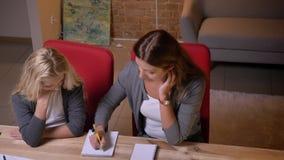 教她的小俏丽的白肤金发的女孩和帮助她的年轻白种人妇女特写镜头画象与家庭作业 股票视频