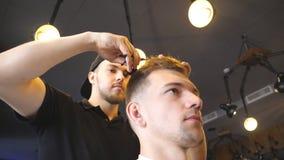 整理他的沙龙的客户的头发的英俊的美发师 梳和剪他的顾客的头发的男性理发师  影视素材
