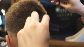 整理客户的头发的理发师的胳膊在理发店 梳和剪顾客的头发的美发师的男性手 股票录像