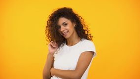扭转在手指的卖弄风情的微笑的mixed-race妇女卷毛,挥动在照相机 股票视频