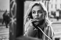 打一次重要电话的年轻美丽的白肤金发的妇女在葡萄酒公共电话电话亭在一个晴朗的晚上 免版税库存图片