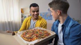 打开箱子用学生党的,食物交付比萨的两个多种族朋友 股票视频