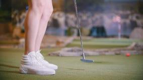 打微型高尔夫球的年轻女人户内 在白色运动鞋的脚 股票录像