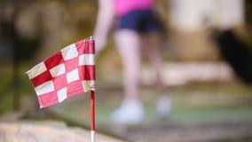 打微型高尔夫球的年轻女人 在前景的完成的旗子 股票录像