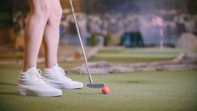 打微型高尔夫球的年轻女人 在框架的腿 股票视频