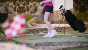 打微型高尔夫球的年轻女人 在blured前景的完成的旗子 股票录像