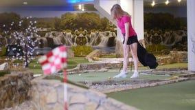 打微型高尔夫球的年轻女人 击中数的妇女连续高尔夫球 股票录像