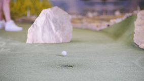 打微型高尔夫球的年轻女人 击中高尔夫球和错过的妇女 股票视频