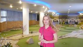 打微型高尔夫球的年轻女人 走在域 股票录像