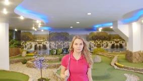 打微型高尔夫球的年轻女人 走在看在照相机的领域 股票录像