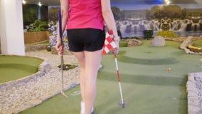 打微型高尔夫球的年轻女人 采取结束旗子和交换结束孔 影视素材