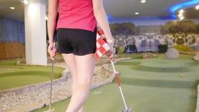 打微型高尔夫球的年轻女人 采取结束旗子和立场它在孔附近 股票视频
