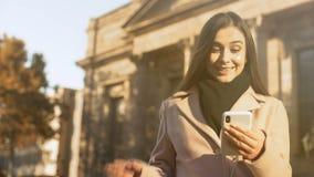 打视频通话的愉快的花姑娘,站立在老大厦附近,技术 股票视频