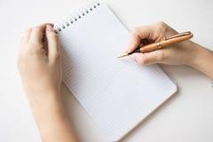 手中的笔记本和的笔 背景查出的白色 免版税图库摄影