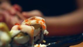 手女孩用棍子采取寿司 中国棍子寿司卷的概念在一块黑暗的板材的 股票录像