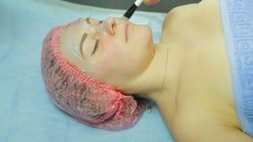 手套的一名美容师与刷子应用在妇女的面孔的泥面具 侧视图 股票录像