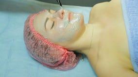 手套的一名美容师投入客户的面孔一个医治用的面具 影视素材