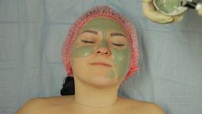 手套的男性美容师应用与一把刷子的泥面具在一个女性客户的面孔 影视素材