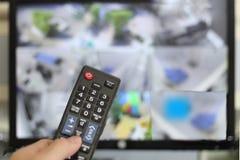 手扶遥控CCTV或闭路电视的在迷离显示器屏幕背景前面 免版税库存图片