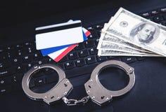 手铐,金钱,在键盘的信用卡 网络罪行和网上欺骗的概念 免版税库存图片