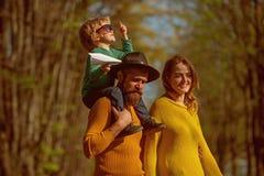 扛在肩上小孩的母亲和父亲感到自由在新鲜空气 幸福家庭一起花费时间 自由是 免版税图库摄影