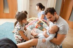 所有家庭父亲、母亲、花费时间的两个女儿和一点小儿子在地毯上在屋子里 免版税库存图片