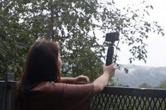 拍森林的照片年轻女性旅行家,使用照相机的山景 免版税库存图片
