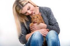 拥抱她美丽的红头发人猫的年轻女人 对动物的爱 库存照片