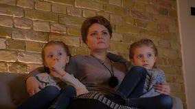 拥抱她的两个害怕的女儿和观看在舒适家庭环境的白种人母亲家庭画象恐怖电影 股票录像