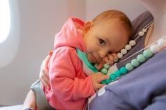 拥抱妈妈的婴儿婴孩第一次坐在飞机 抱着她的婴孩的母亲和安全带在飞行期间 免版税库存照片