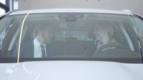 拥抱在从售车行的一辆最近被购买的新的汽车的快乐的愉快的成功的夫妇 汽车陈列室 影视素材