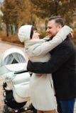拥抱在秋天公园的妈妈和爸爸 免版税库存图片