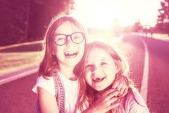 拥抱和微笑反对日落的两个快乐的女孩 免版税库存图片