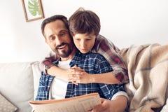 拥抱爸爸的父亲和一点儿子在家男孩坐有谈论的报纸的沙发新的愉快的特写镜头 免版税图库摄影