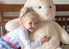 拥抱被充塞的兔宝宝的复活节礼服的逗人喜爱的女孩 免版税库存照片