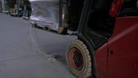拾起有商品的铲车司机箱子在大仓库里