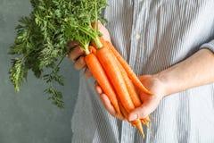 拿着与上面的农夫人成熟红萝卜 免版税库存照片