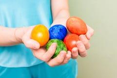拿着五颜六色的鸡蛋的女孩 明亮的复活节彩蛋在妇女的手上 特写镜头 库存照片