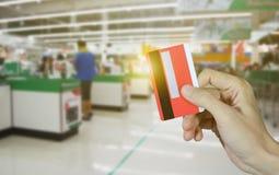 拿着信用卡和超级市场商店摘要被弄脏的背景,网络购物概念的手 免版税库存图片