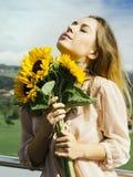 拿着向日葵的愉快的美丽的年轻女人 库存照片