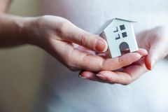 拿着微型白色玩具房子的女性妇女手 免版税库存图片