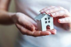 拿着微型白色玩具房子的女性妇女手 免版税图库摄影