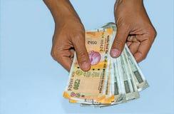 拿着全新的200和500卢比的人的手印度钞票 免版税图库摄影