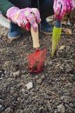 拿着园艺工具的女孩 免版税图库摄影