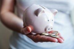 拿着桃红色存钱罐和欧元硬币的妇女手 免版税图库摄影
