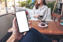 拿着有空白的白色屏幕的一个人的手黑手机有坐在咖啡馆的妇女的 图库摄影